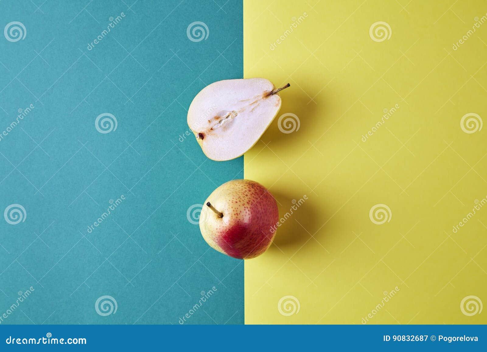 两整个新鲜的梨,果子从上面切成了两半看法在绿色黄色背景,现代样式食物图片,样式设计