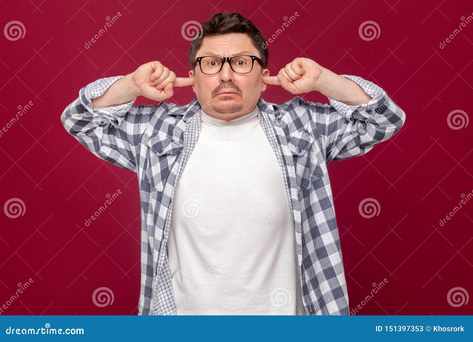严肃的中间年迈的商人画象偶然方格的衬衣的,镜片身分,投入手指在耳朵,并且不要