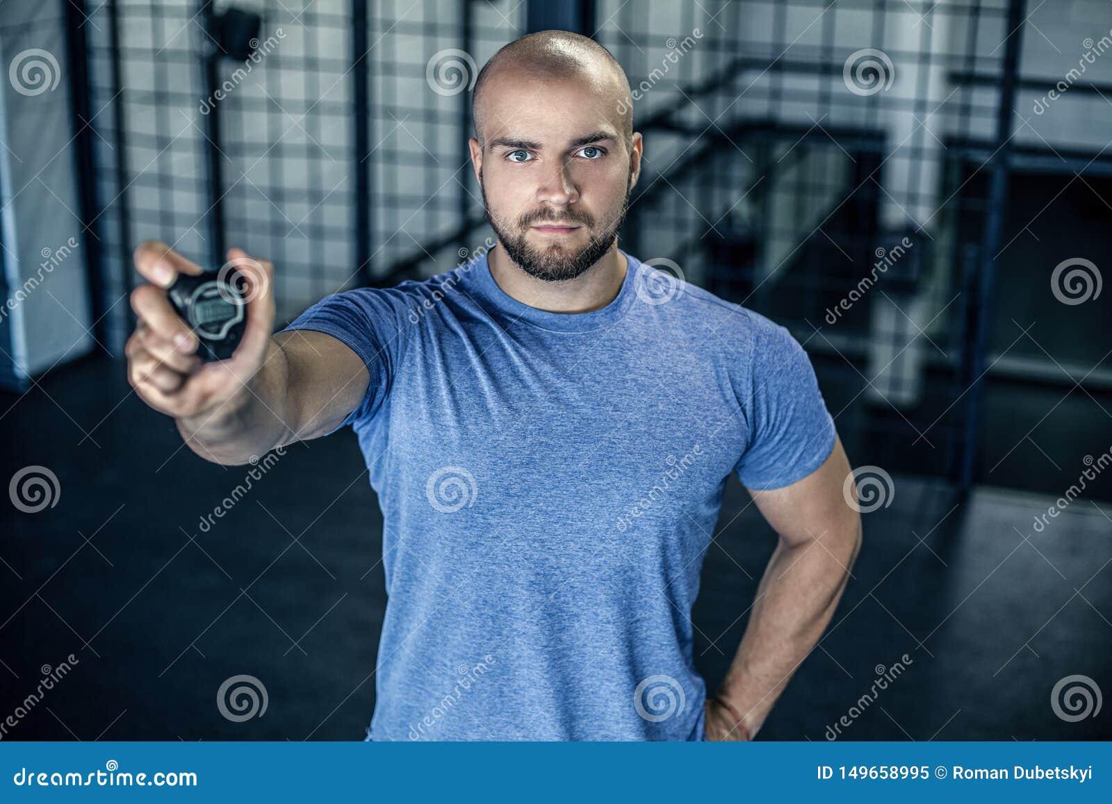 严肃的体育教练的画象有一个秃头的 在健身房的照相机显示一块秒表 锻炼是成功的 ??
