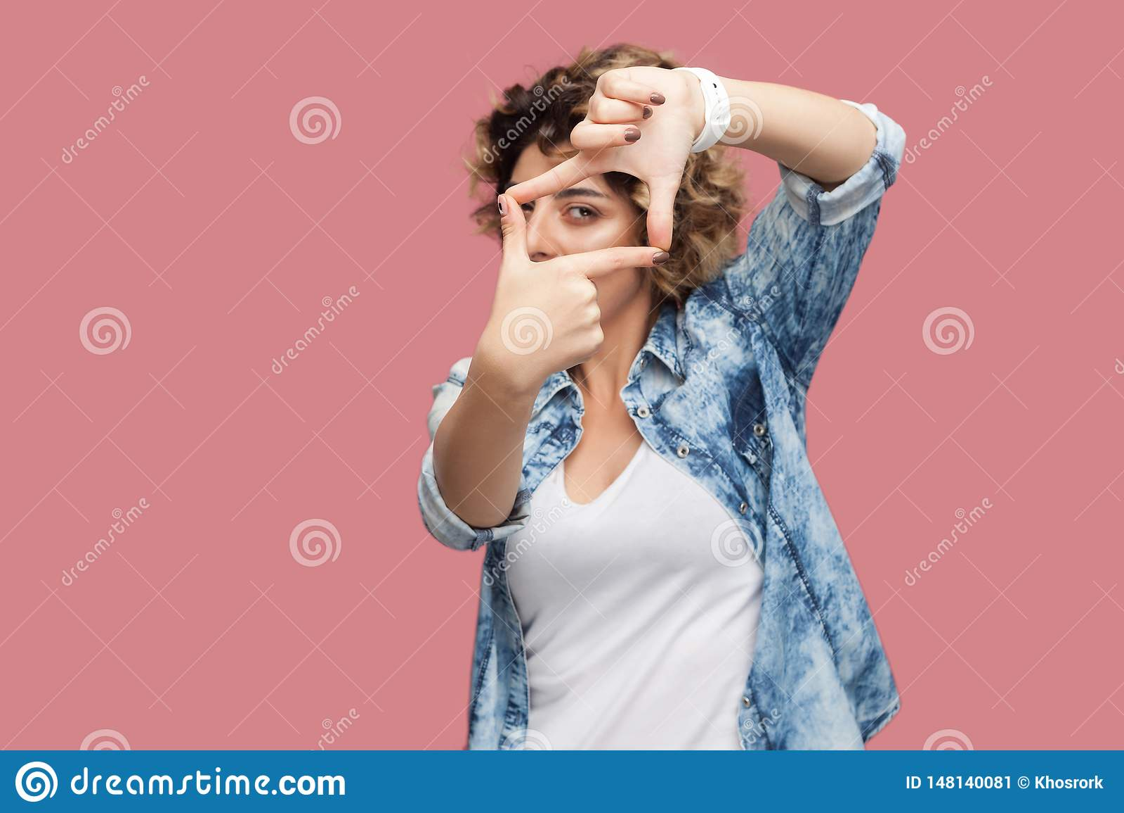 严肃的殷勤年轻女人画象有卷曲发型的在与庄稼手构成的偶然蓝色衬衣身分和