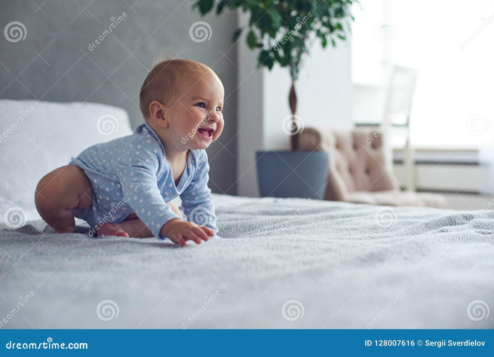8个在家爬行在床上的月大愉快的男婴