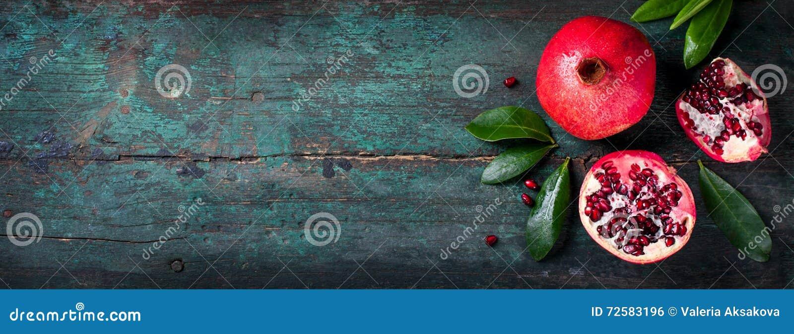 整个新鲜的水多的石榴-和裁减,与在木葡萄酒背景的叶子,顶视图,水平