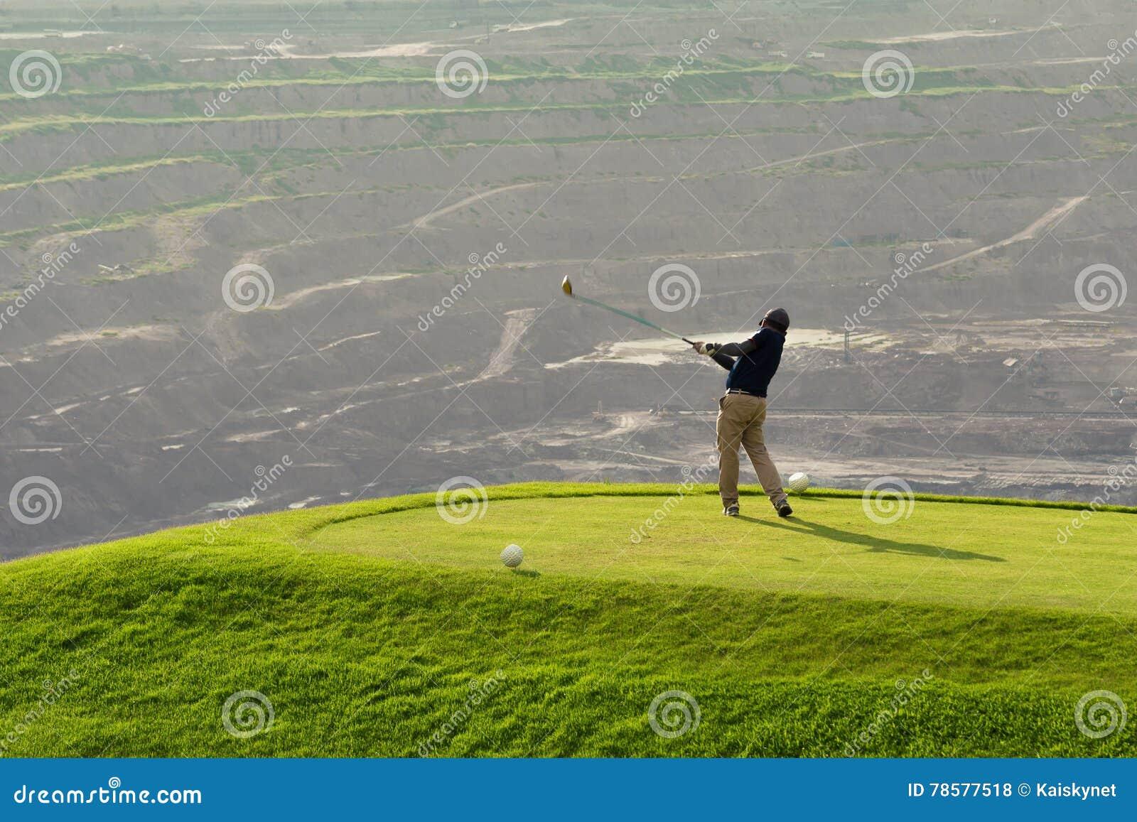 击中与俱乐部的高尔夫球运动员球在Beatuiful高尔夫球场