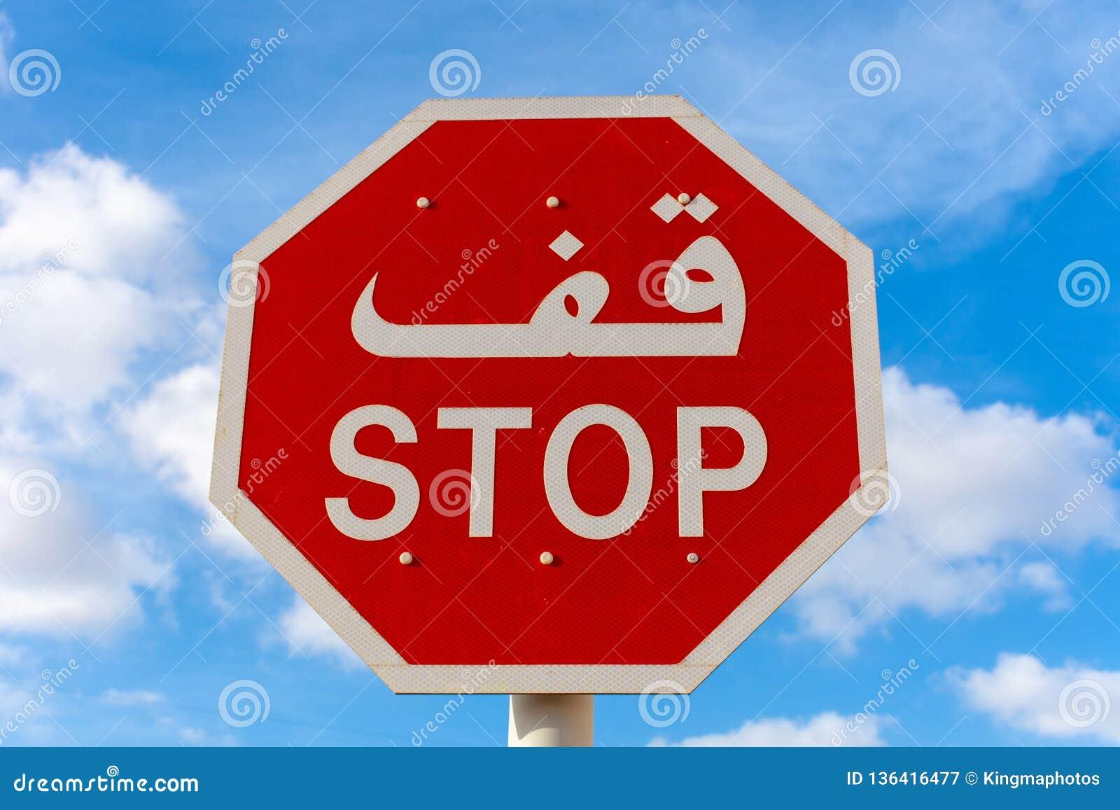 中止签字用英语和阿拉伯与天空蔚蓝和云彩在背景中