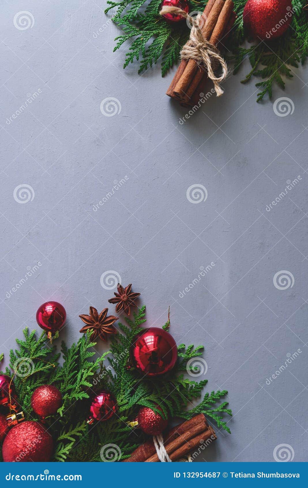 中看不中用的物品蓝色圣诞节构成玻璃 圣诞节杉树分支、球、肉桂条和茴香星在灰色木背景 平的位置