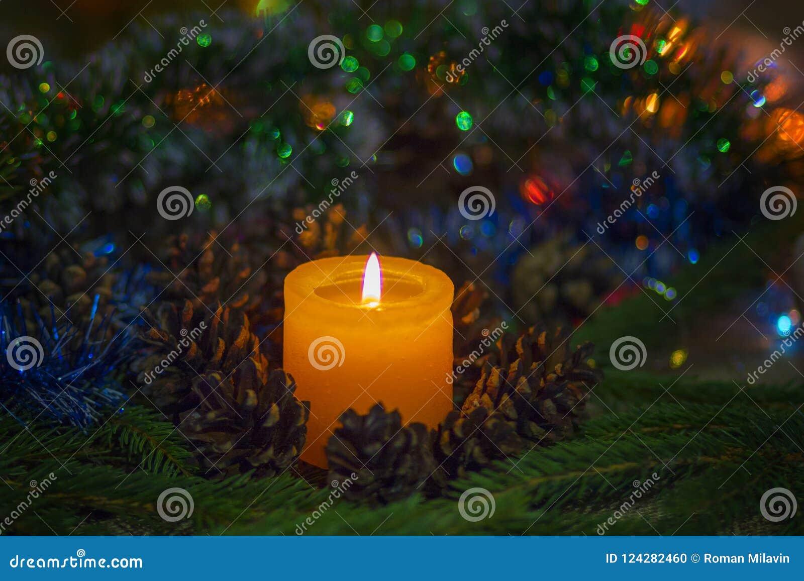 中看不中用的物品蓝色圣诞节构成玻璃 在杉木锥体和冷杉附近的一个灼烧的蜡烛分支 与一整洁的bokeh的美好的模糊的背景 它` s Al