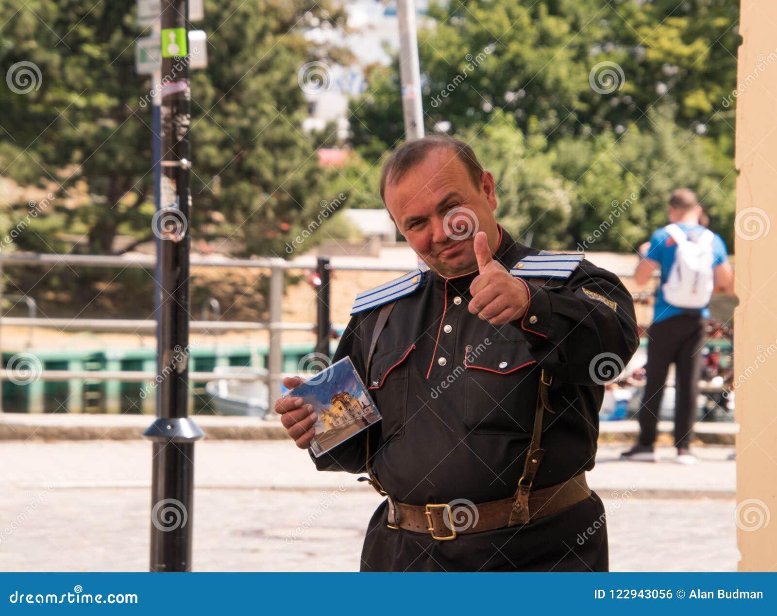 中部变老了德国制服的白种人人微笑和给赞许和拿着CD的盒的