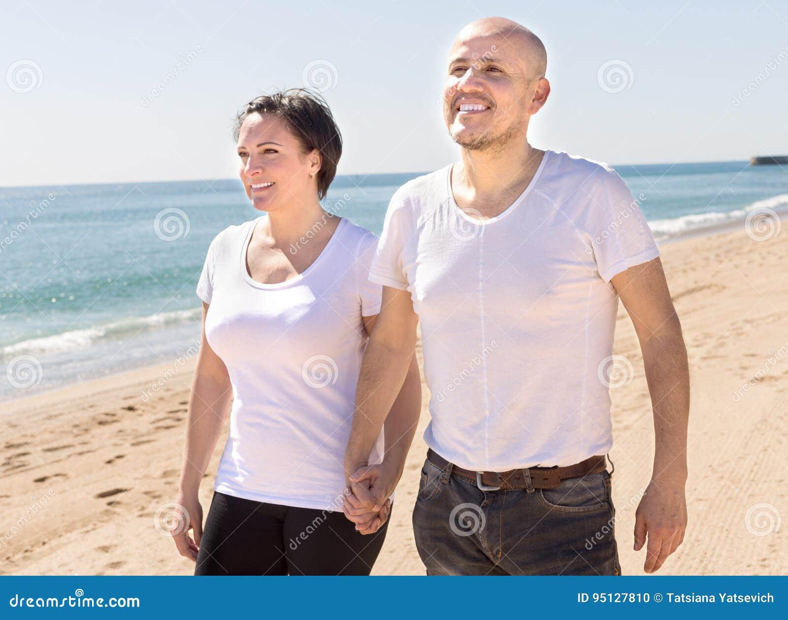 中年白色T恤杉的走在海滩的男人和妇女