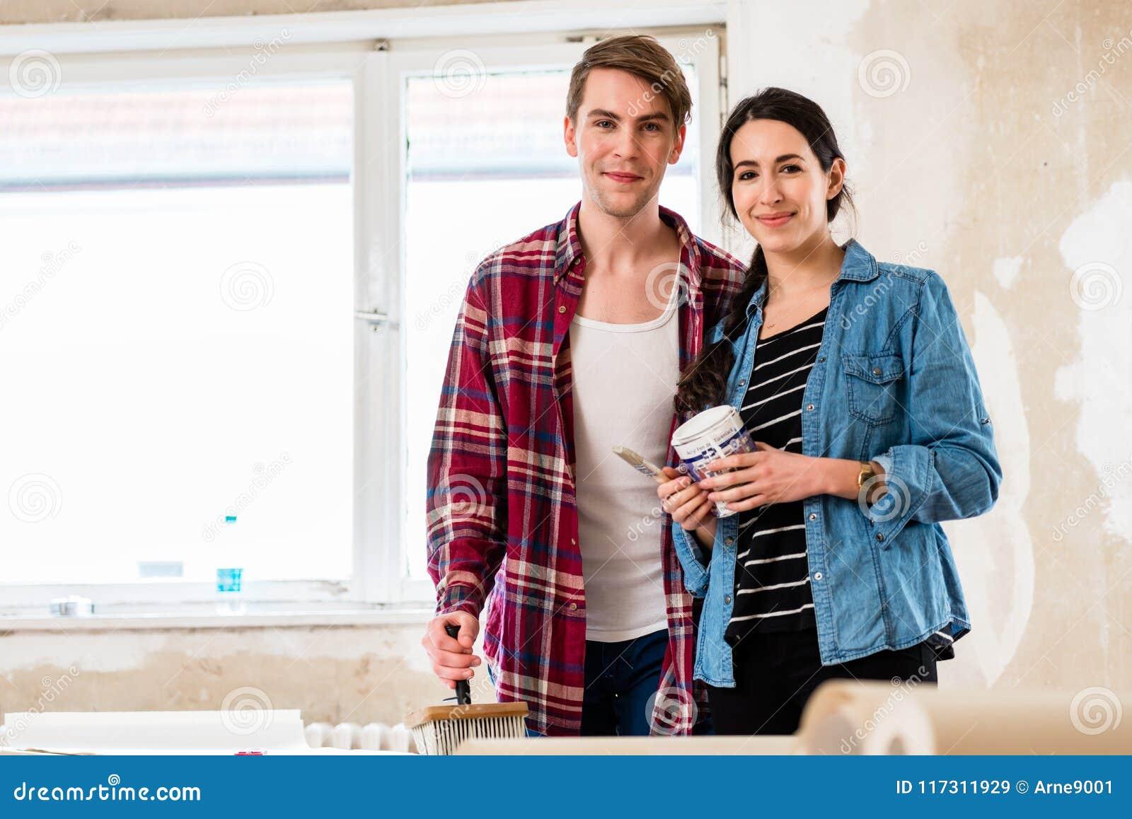 为家庭改造的愉快的年轻夫妇夹具的画象