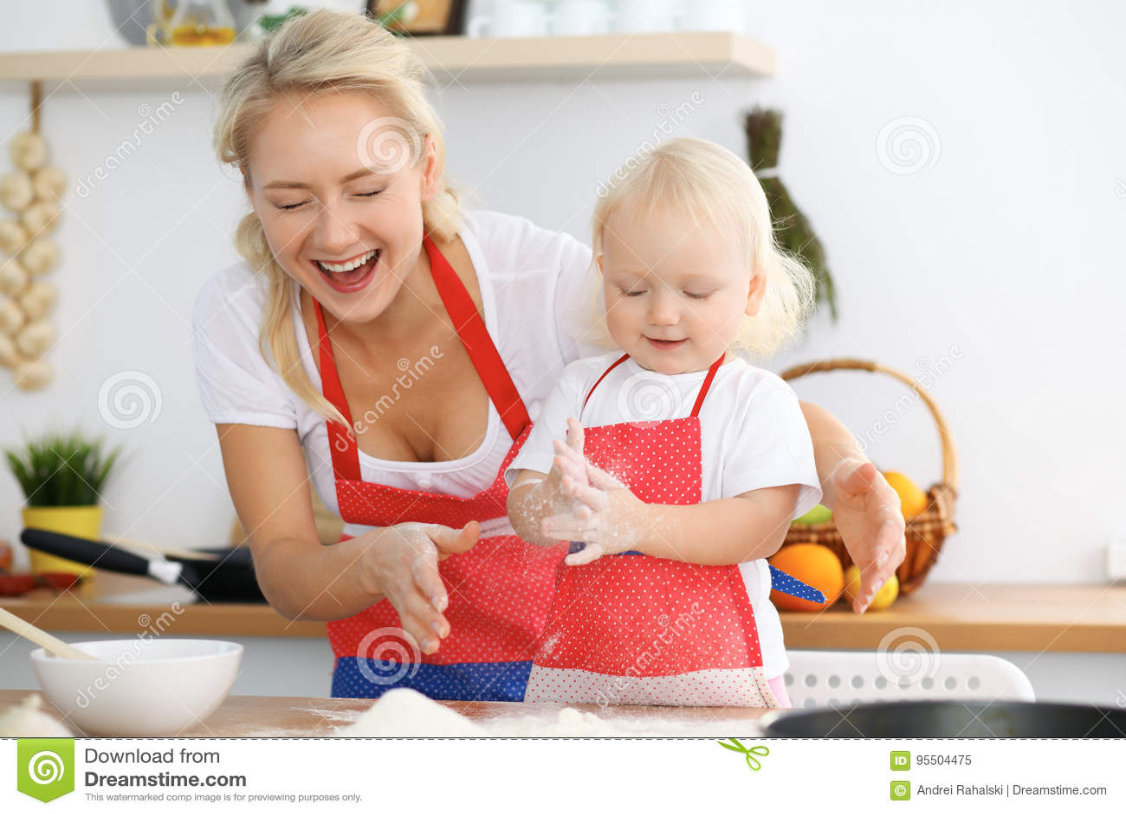 为母亲` s天照顾和她的烹调假日饼或曲奇饼的小女儿 愉快的家庭的概念在厨房里