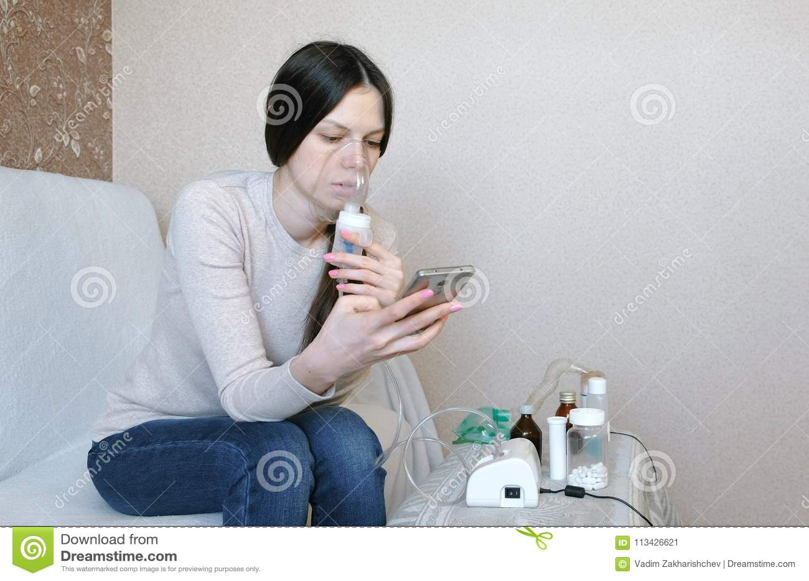 为治疗使用雾化器和吸入器 吸入通过吸入器面具和看电话的少妇 侧视图