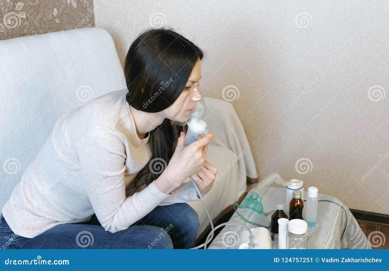 为治疗使用雾化器和吸入器 吸入通过吸入器面具的少妇看一个小瓶药片 端