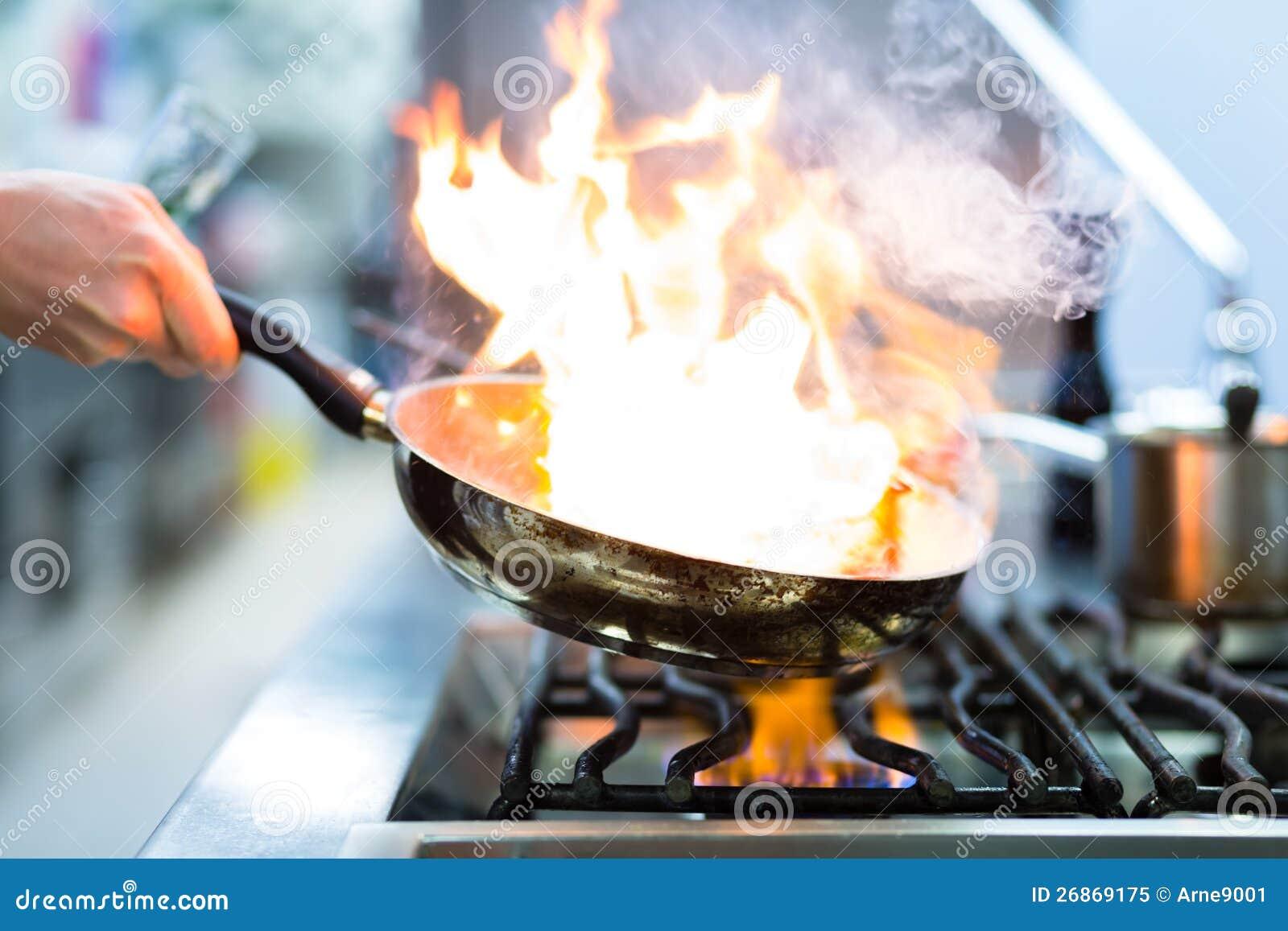 主厨在火炉的餐馆厨房里与平底锅