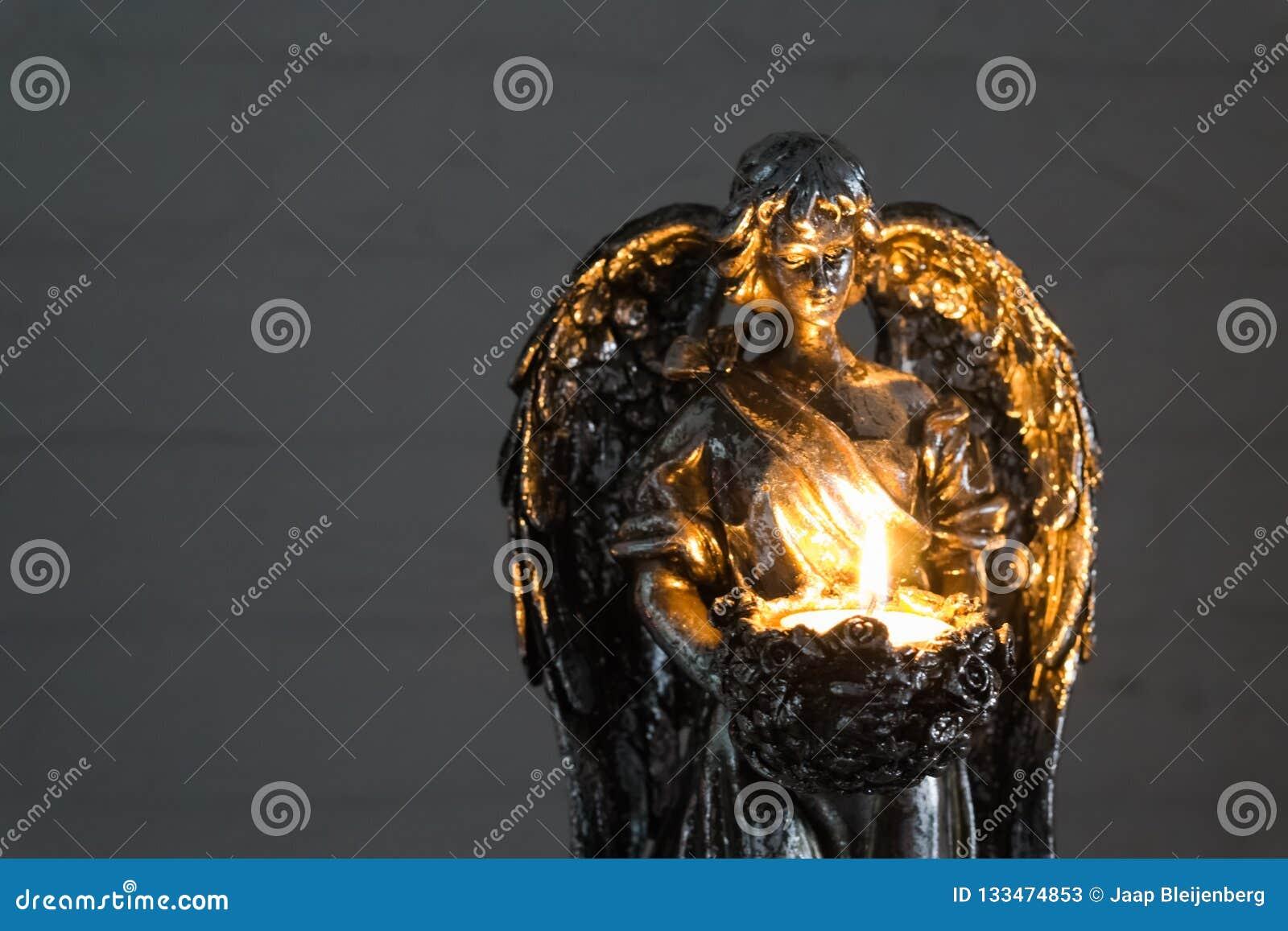 举在特写镜头、圣诞节和精神传统的银色天使雕象一个灼烧的蜡烛