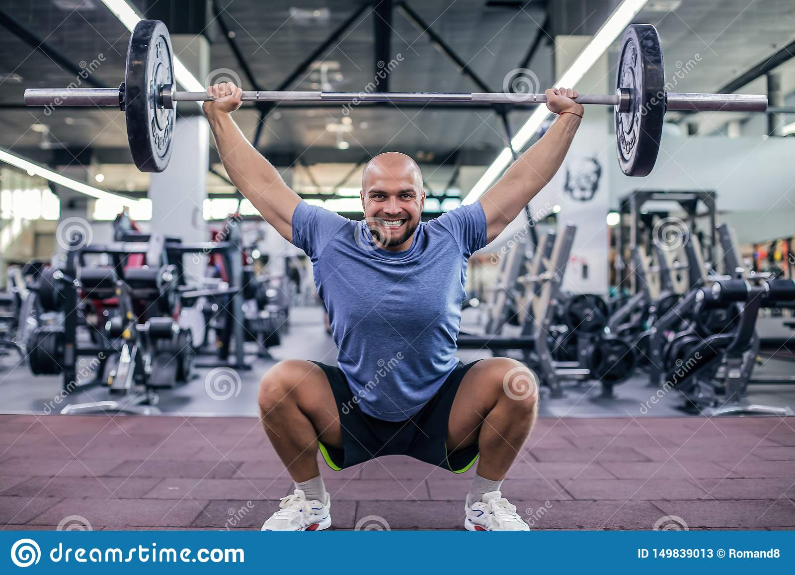 举的重量和尖叫 运动服举的杠铃的年轻帅哥在健身房