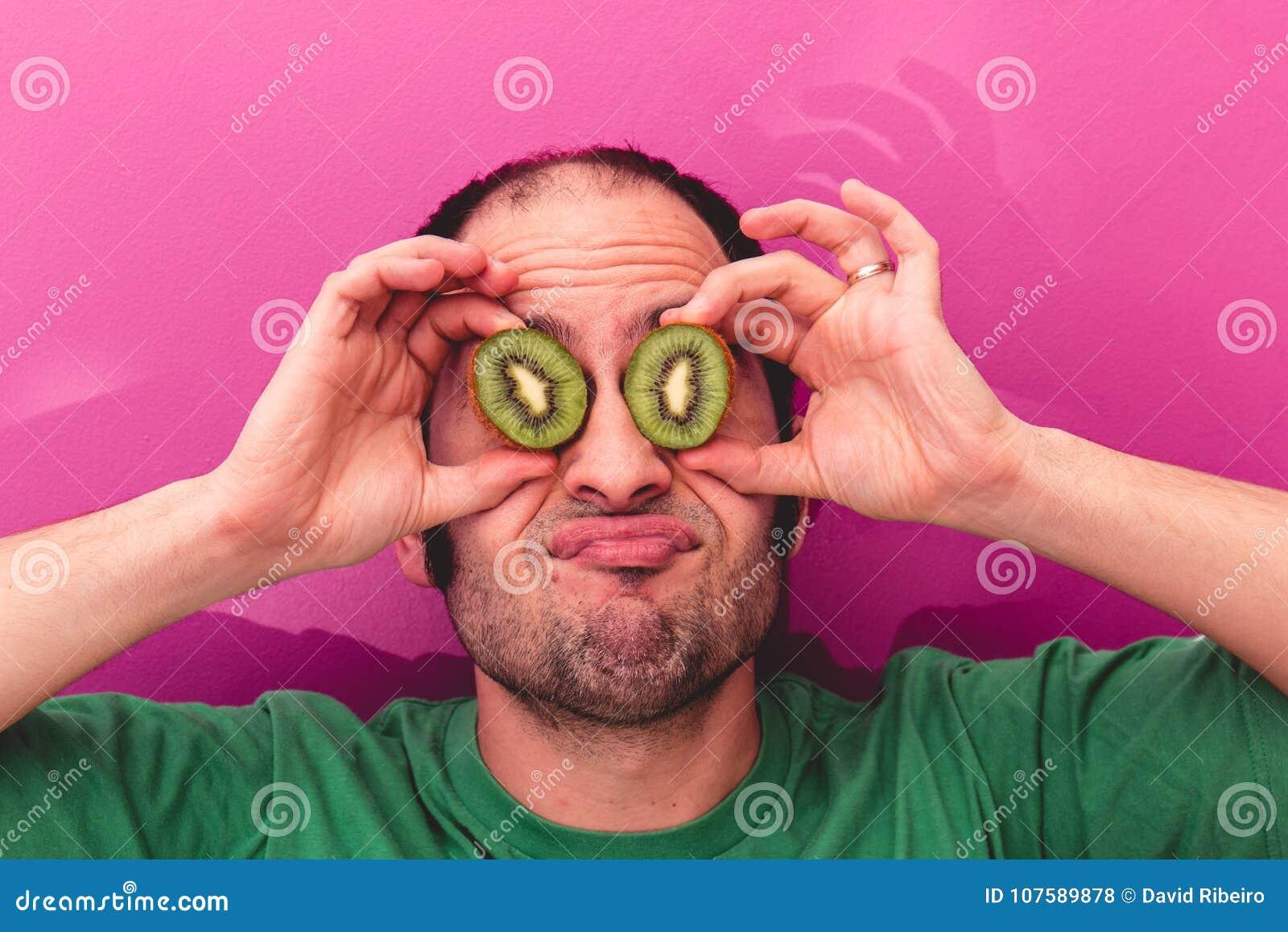 举行两的一个人的画象切了在他的眼睛的猕猴桃
