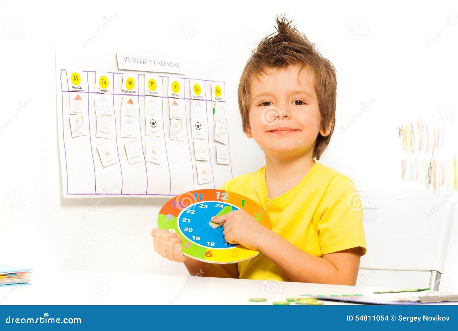 举行五颜六色的纸盒时钟开会的微笑的男孩
