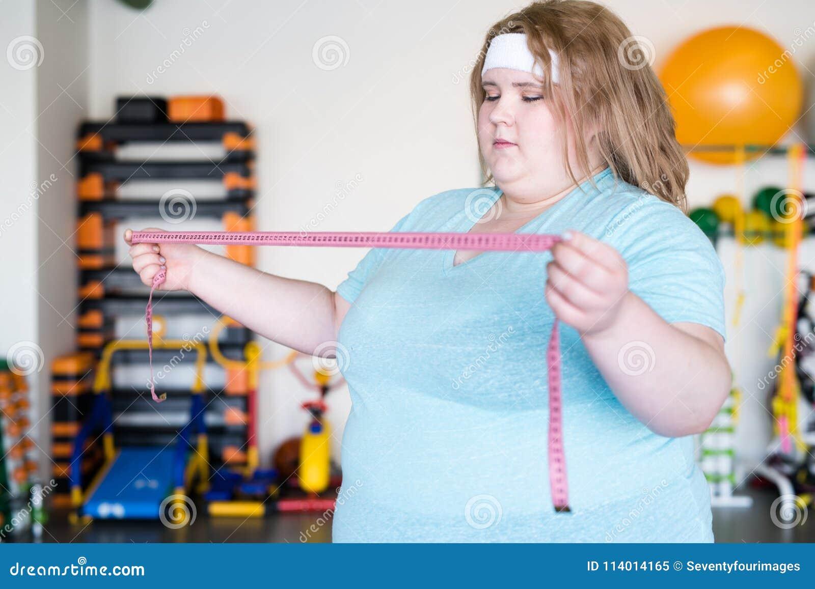 举行卷尺的肥胖妇女
