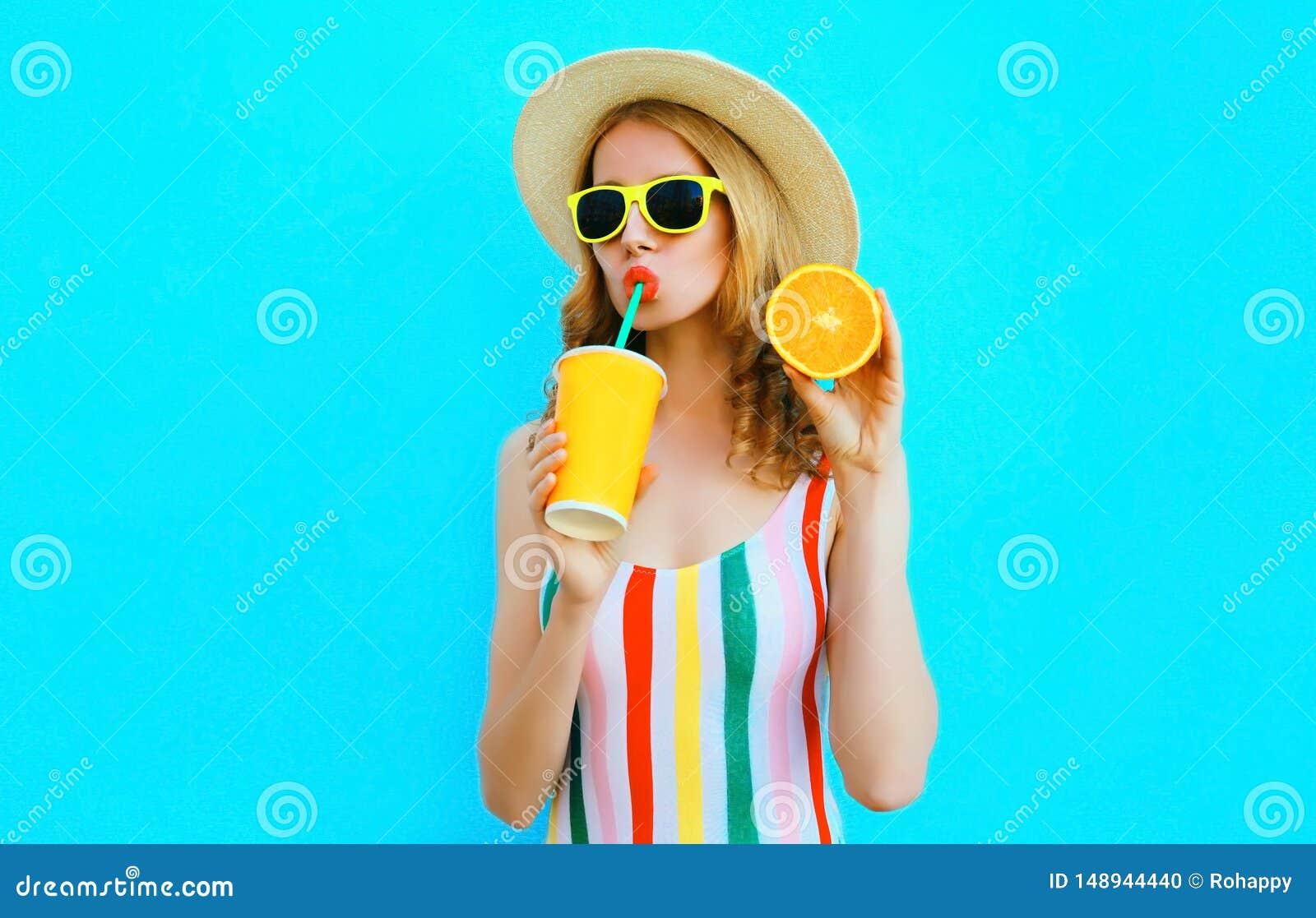 举行在她的手切片的夏天画象妇女饮用的果汁在草帽的桔子在五颜六色的蓝色