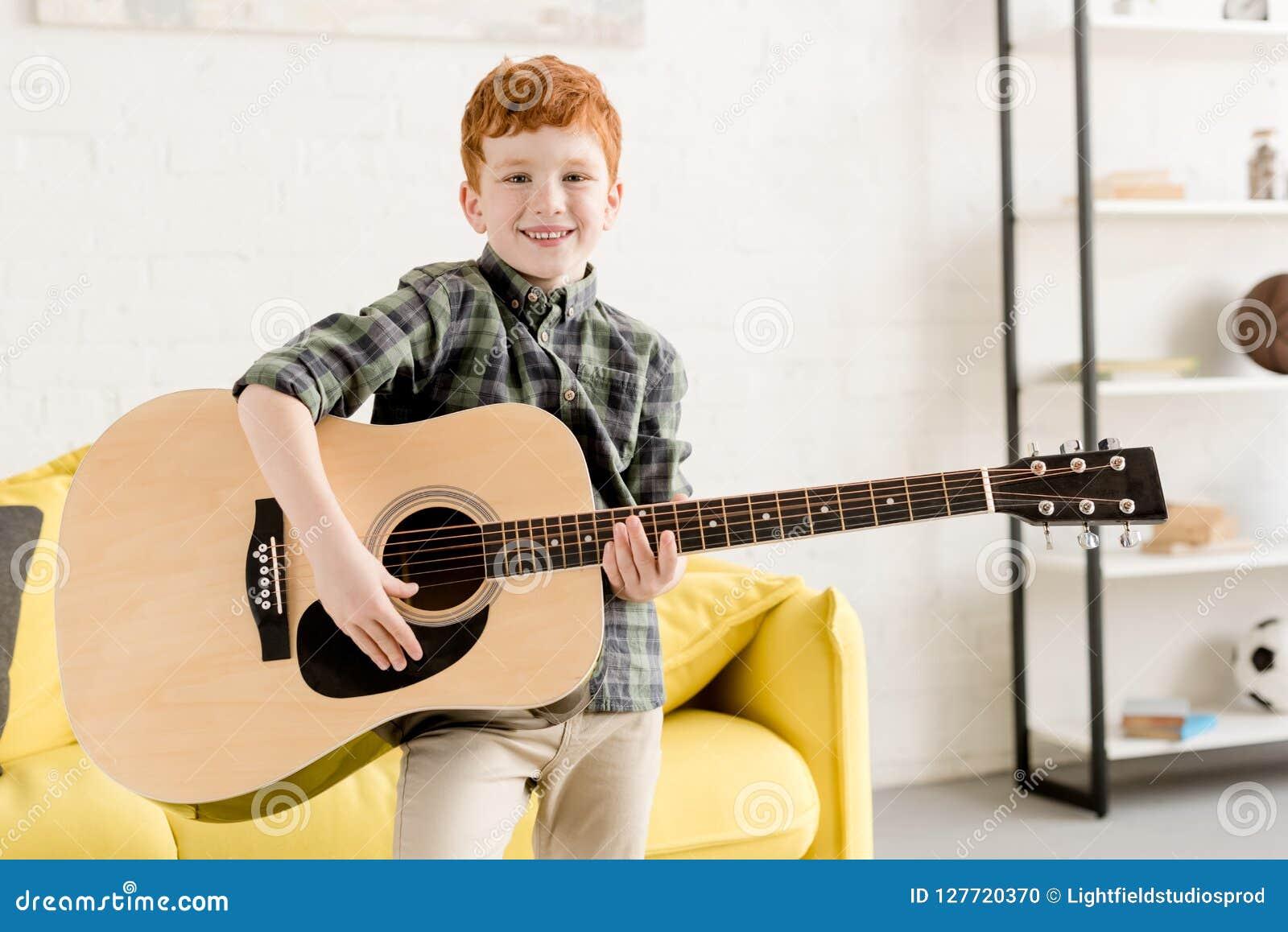 举行声学吉他和微笑的逗人喜爱的小男孩