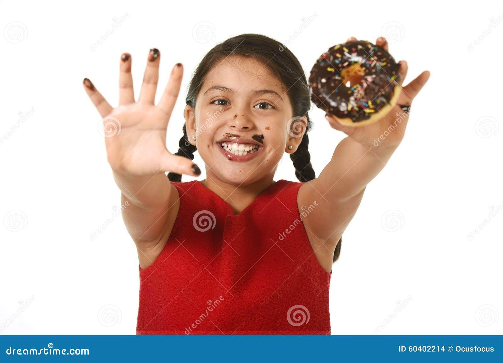 举行巧克力多福饼用手和嘴被弄脏和肮脏显示的微笑的红色礼服的拉丁女孩愉快