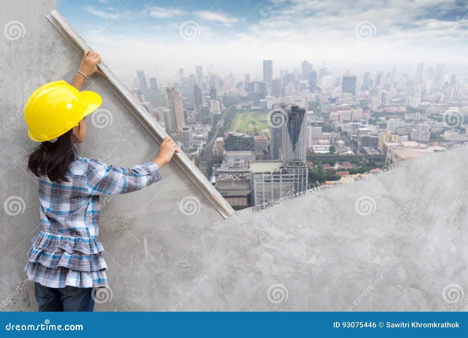 举行涂灰泥的小女孩工程学用工具加工在墙壁上的绘画摩天大楼
