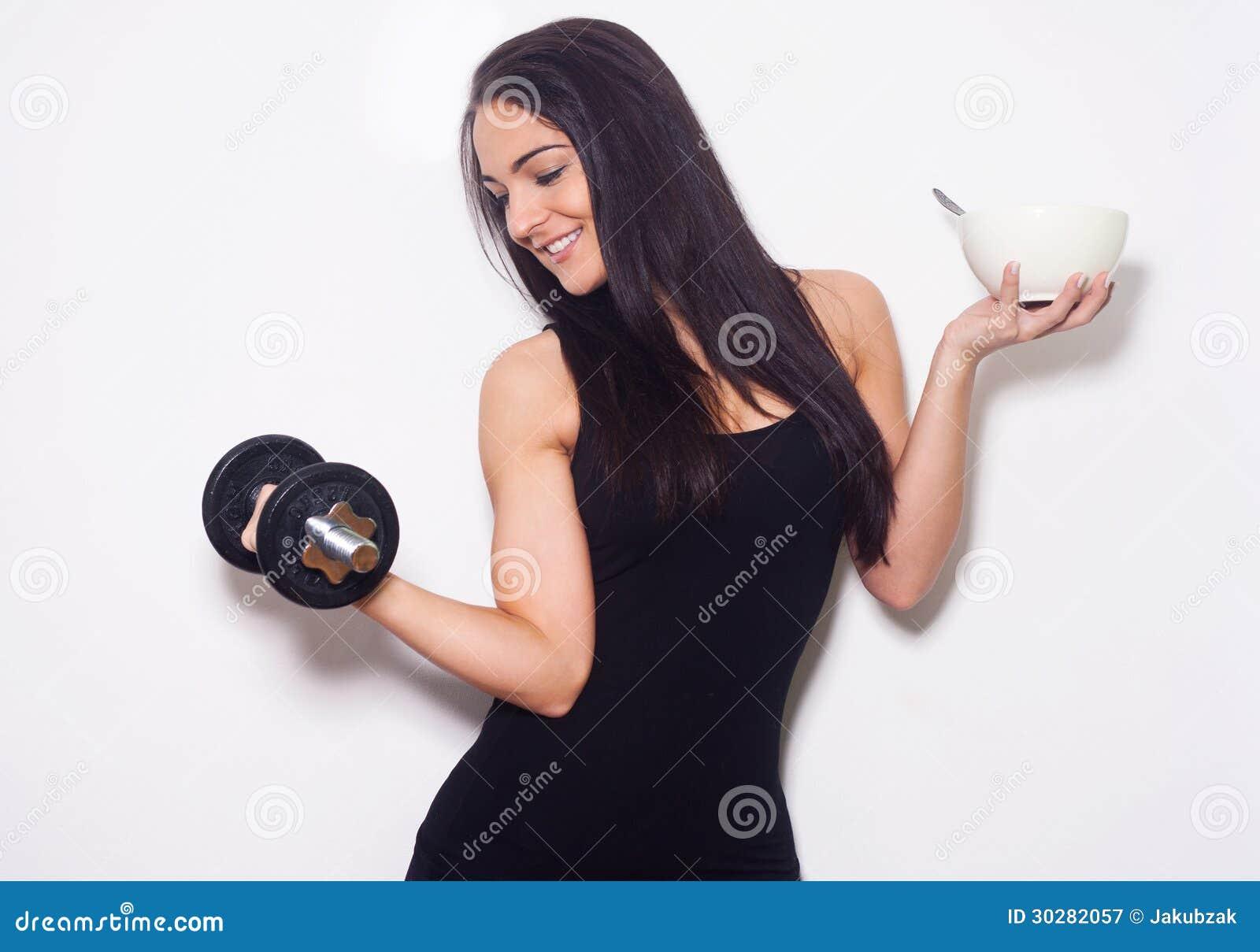 举行碗和哑铃的年轻美丽的妇女。