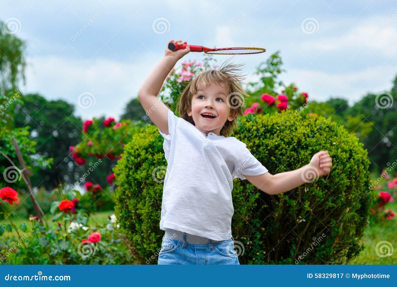 举行羽毛球的愉快的小男孩画象