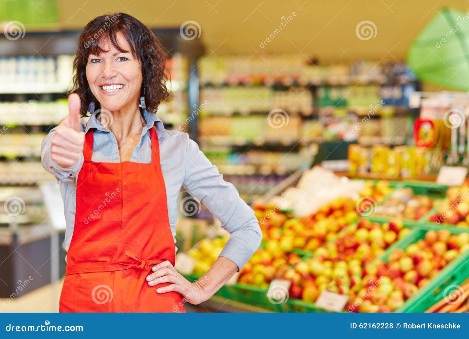 举行她的赞许的愉快的年长女推销员在超级市场.图片