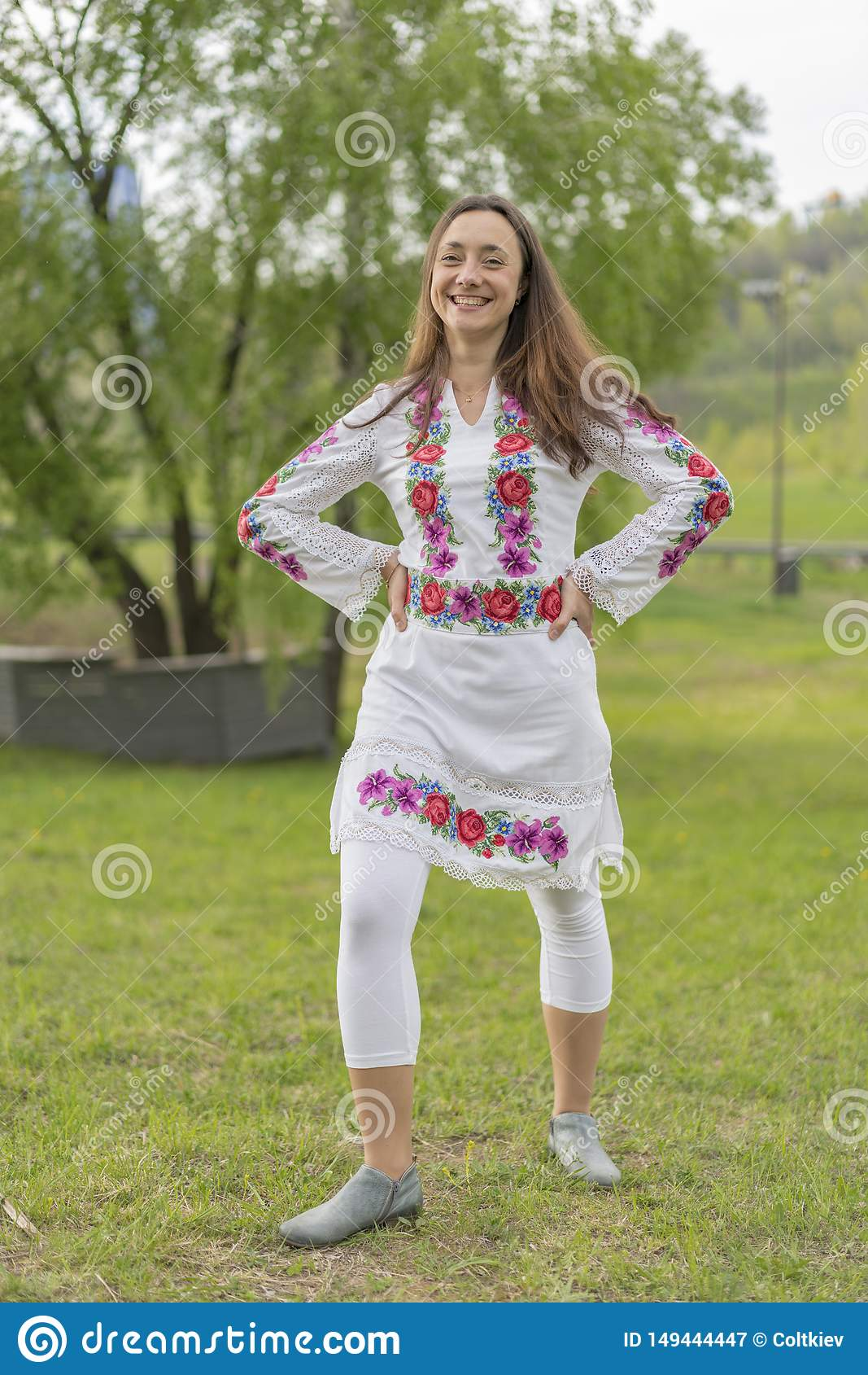 乌克兰全国衣裳的愉快的年轻女人在公园 刺绣的妇女 r