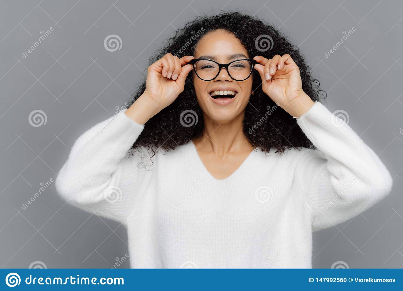 乐观可爱的妇女照片通过眼镜愉快地看,保留在眼镜外缘的手,注意宜人的事,
