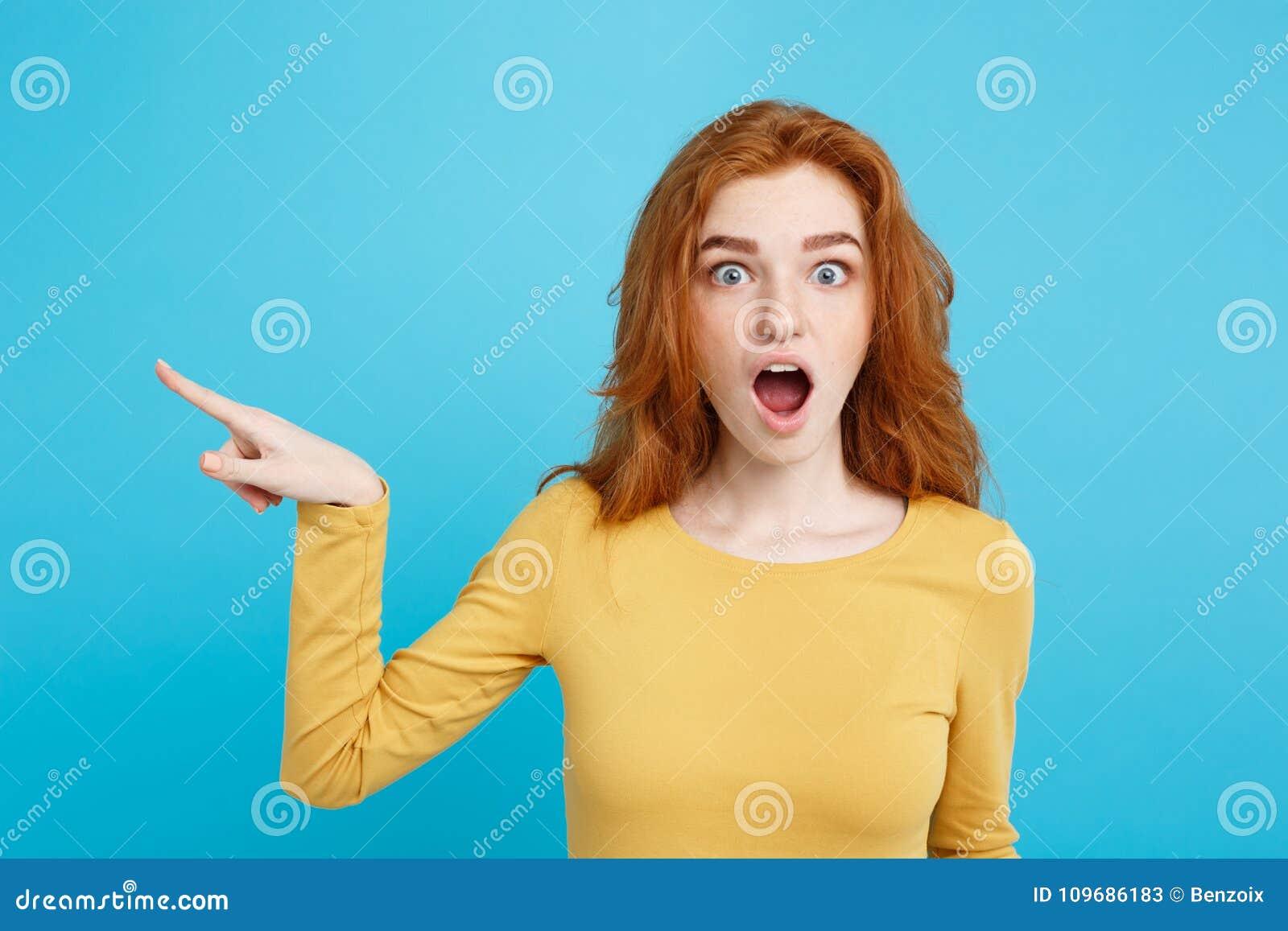 乐趣和人概念-愉快的有指向手指和冲击的姜红色头发女孩特写画象