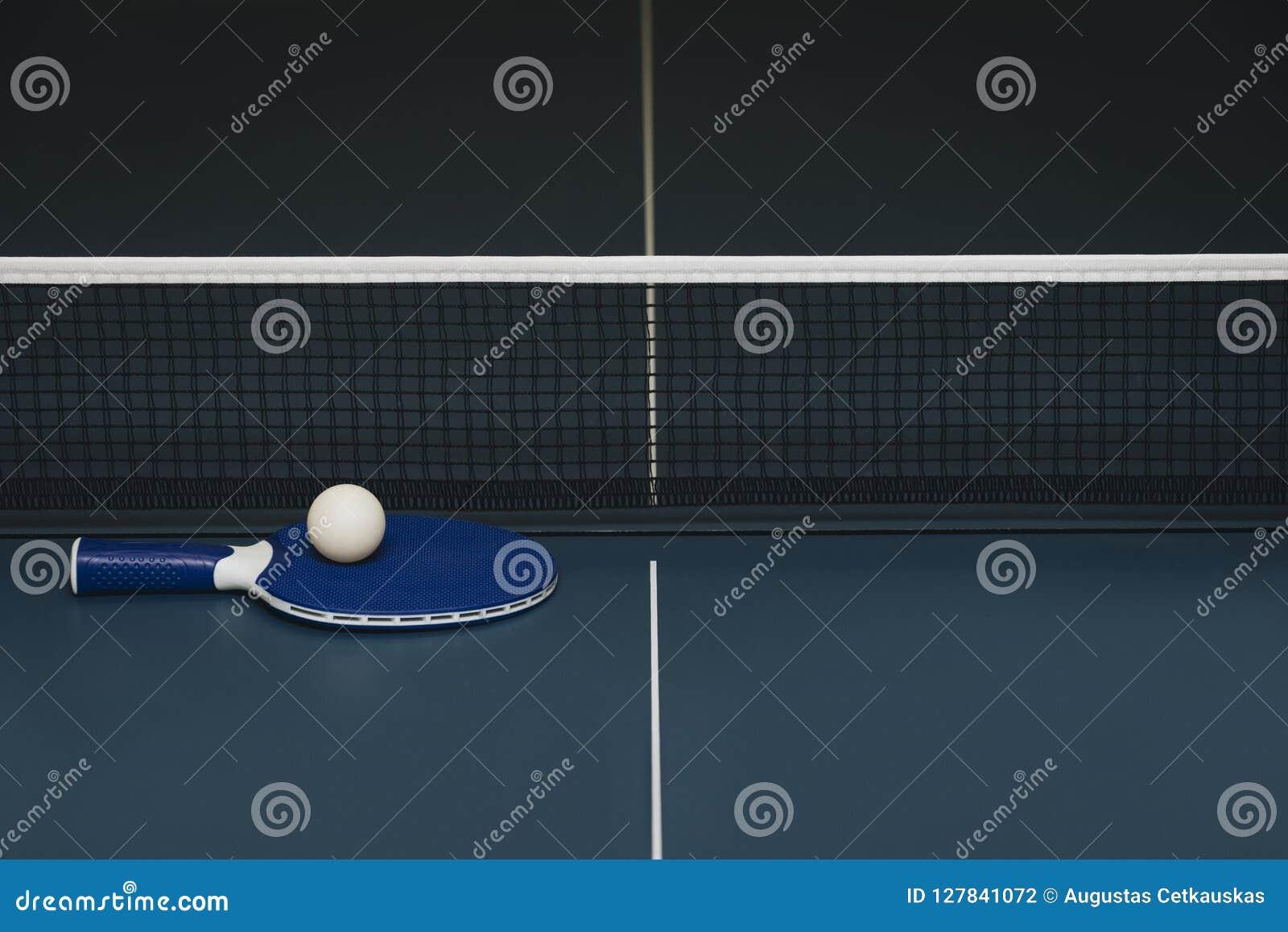 乒乓球球拍和球和网在一个蓝色球台上