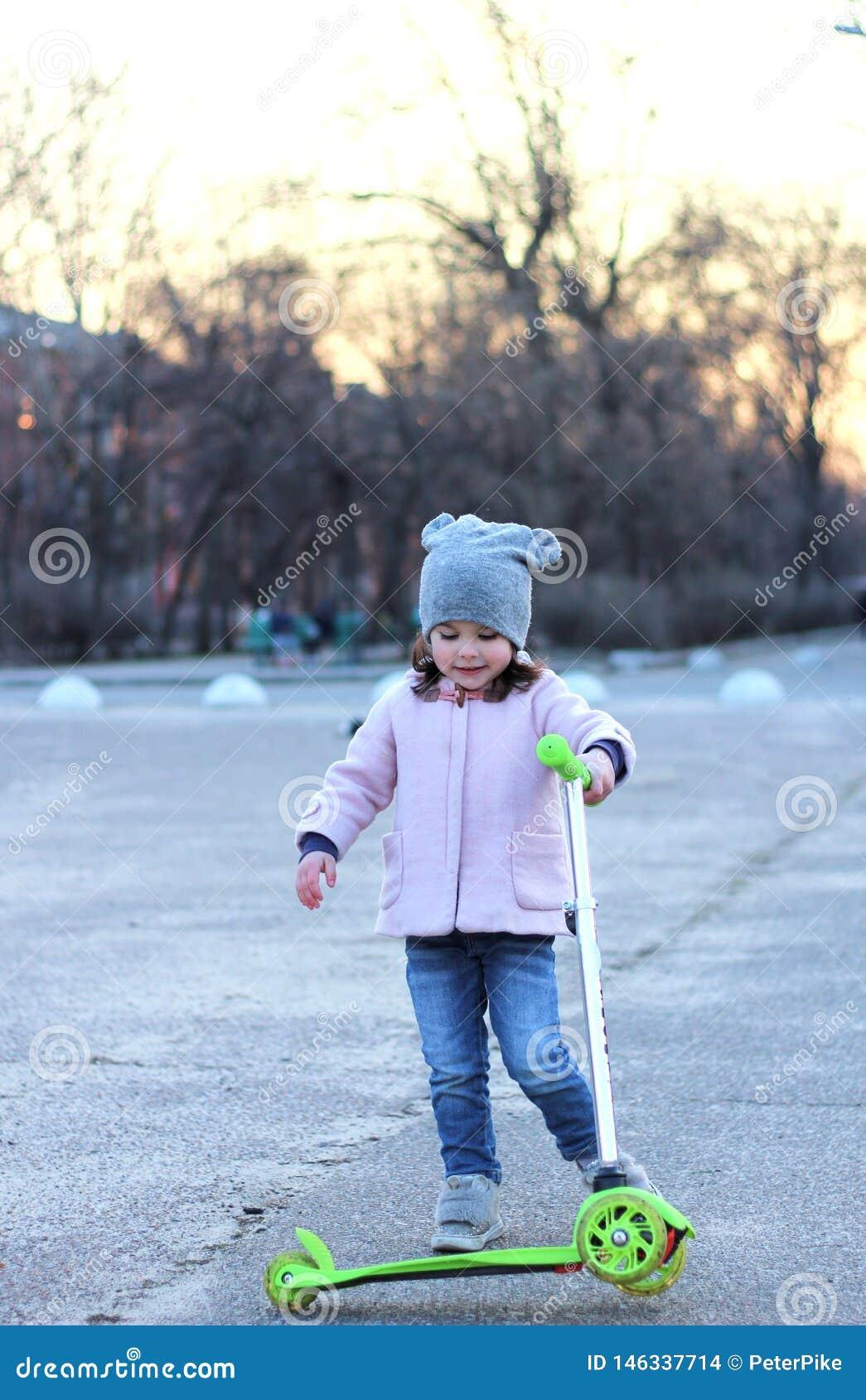 乘坐一辆单轮滑行车的帽子、外套和牛仔裤的逗人喜爱的女孩 春天城市日落
