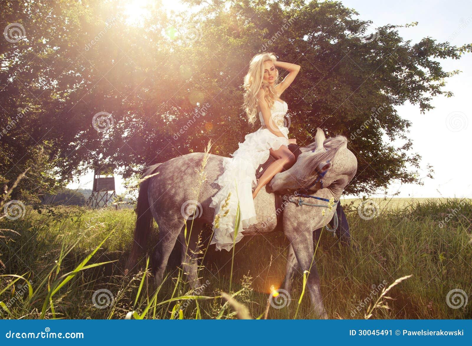 乘坐马的白肤金发的肉欲的新娘美丽的照片。
