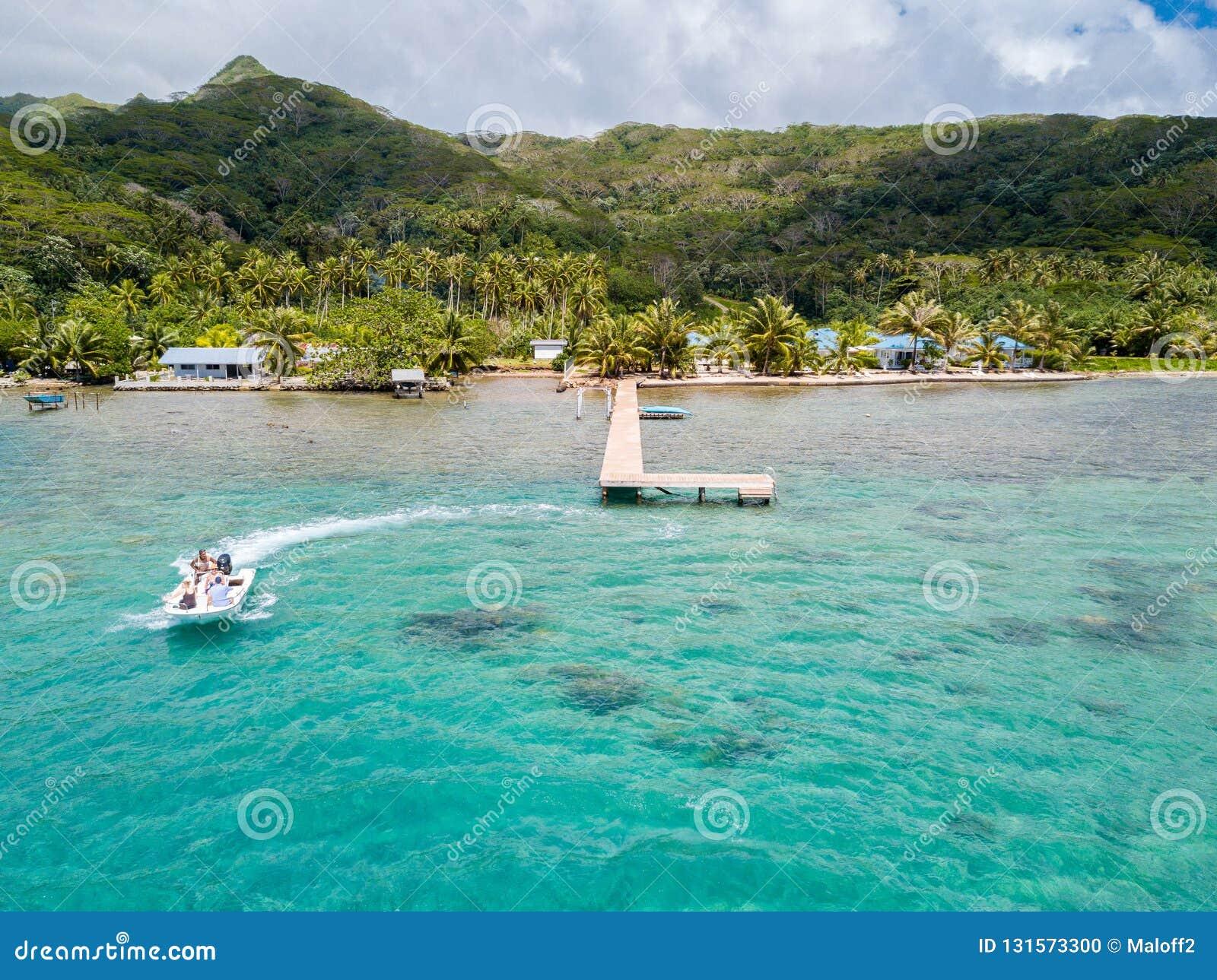 乘坐高速喷气机小船的游人在一个惊人的天蓝色的蓝色绿松石盐水湖 鸟瞰图 Raiatea,法属玻里尼西亚