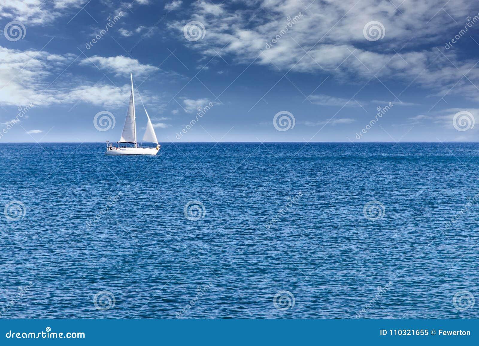 乘快艇单独航行在镇静蓝色海水的风船在与蓝天和白色云彩的一个美好的晴天