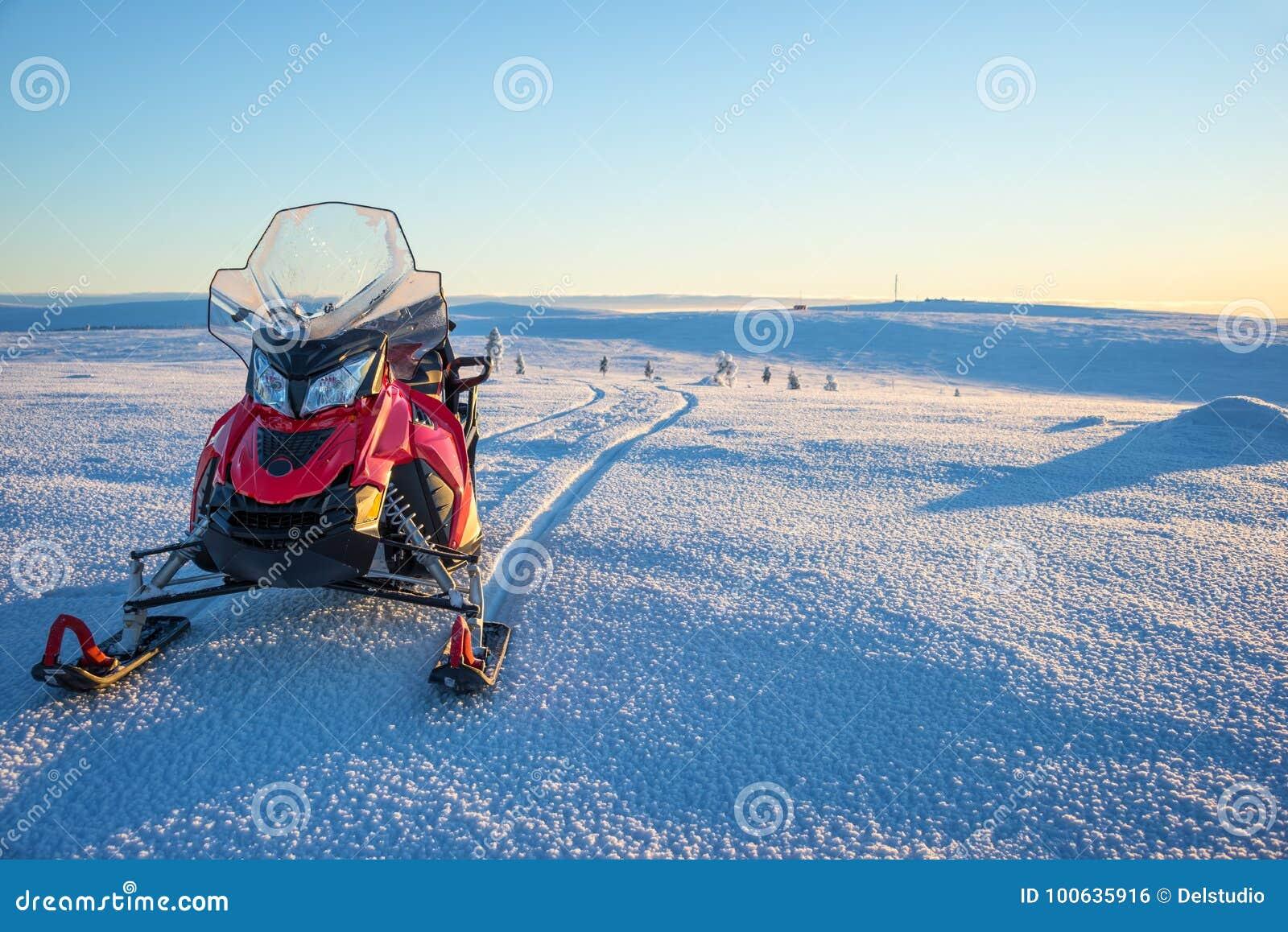 乘雪上电车在一个多雪的风景在拉普兰在Saariselka,芬兰附近