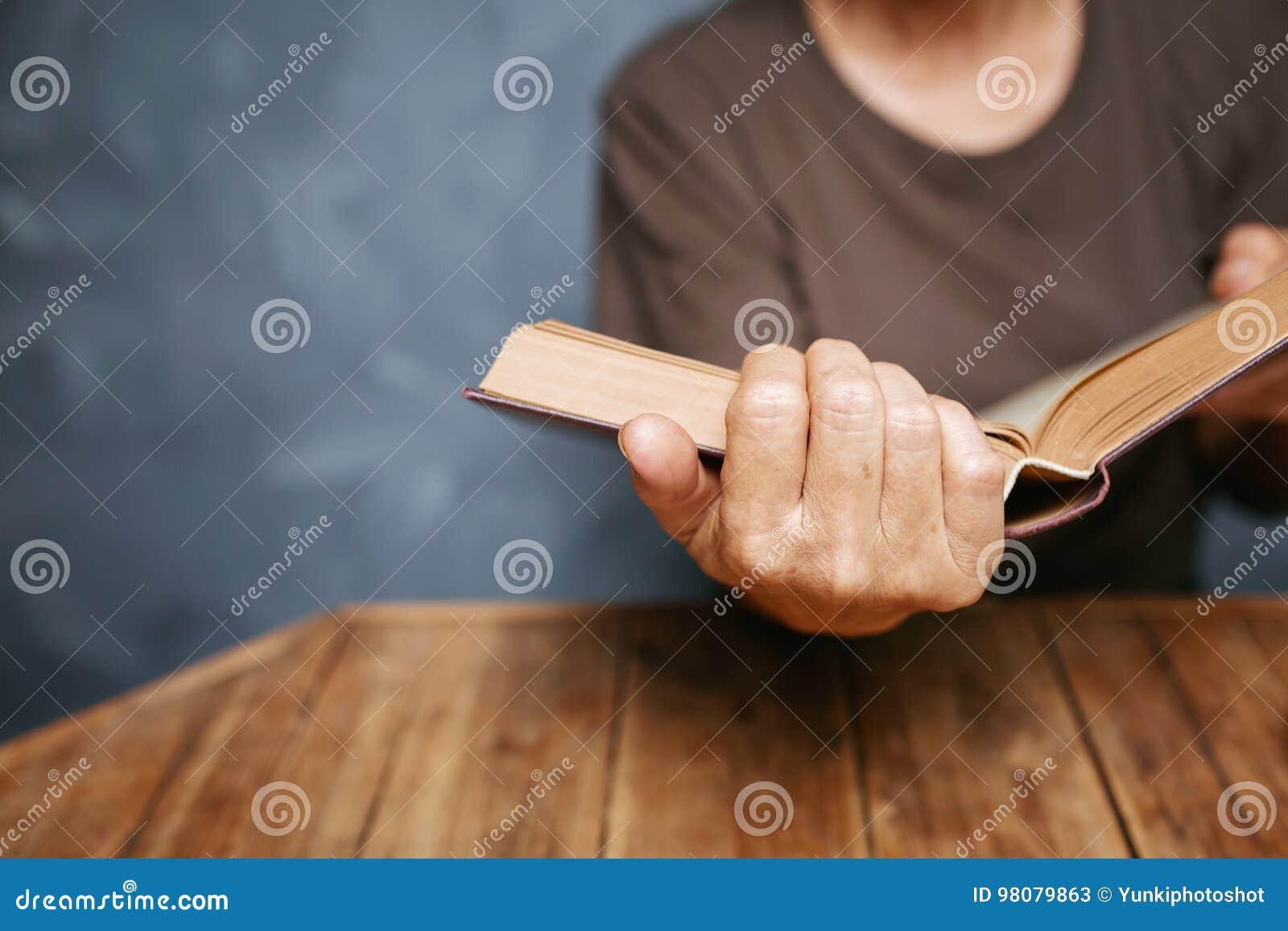 读书的资深妇女在有老葡萄酒tabl的客厅