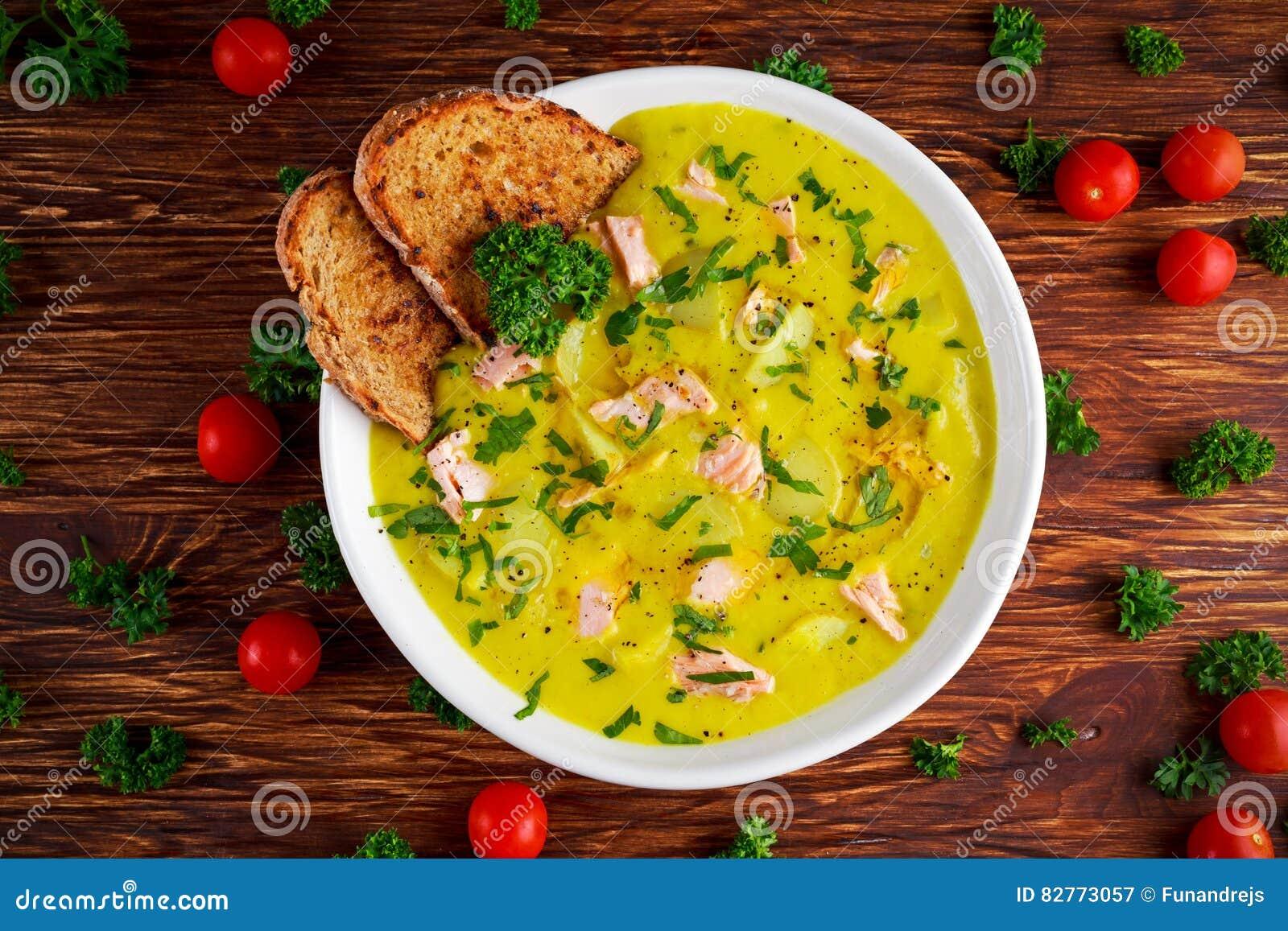 乳脂状的鱼三文鱼,韭葱,在木背景的土豆汤
