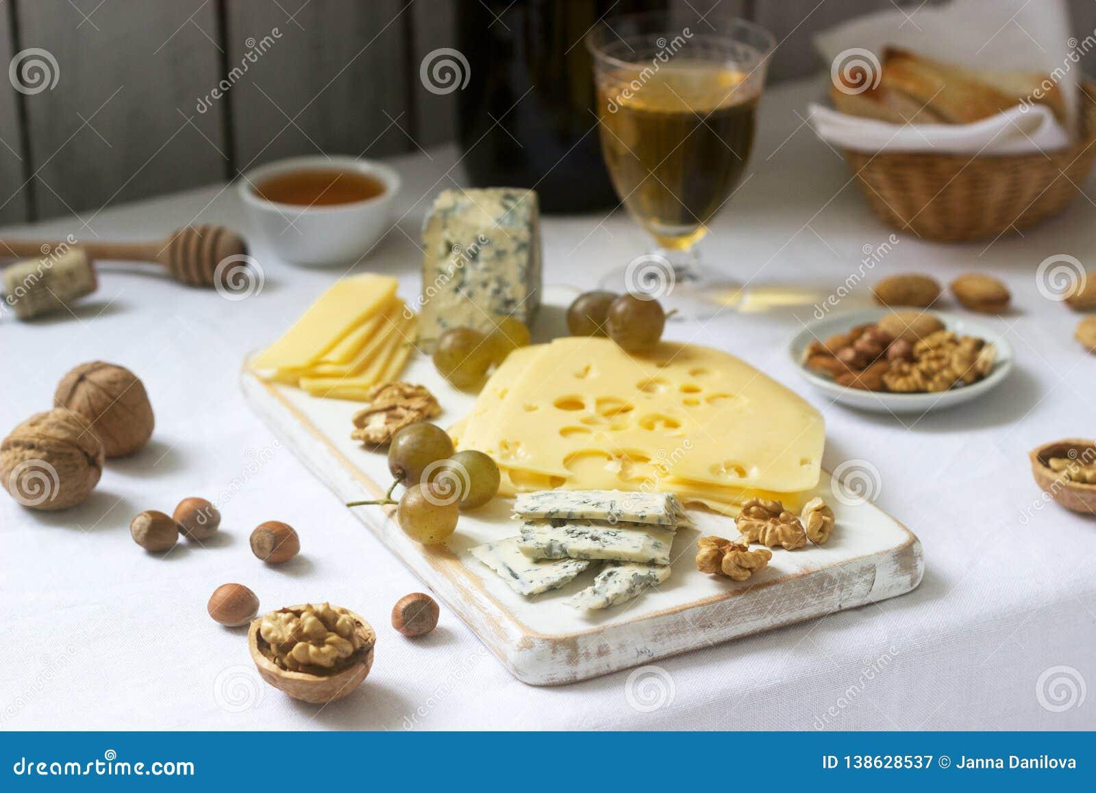 乳酪、葡萄、坚果和蜂蜜的各种各样的类型开胃菜,供食与白色和红酒 土气样式