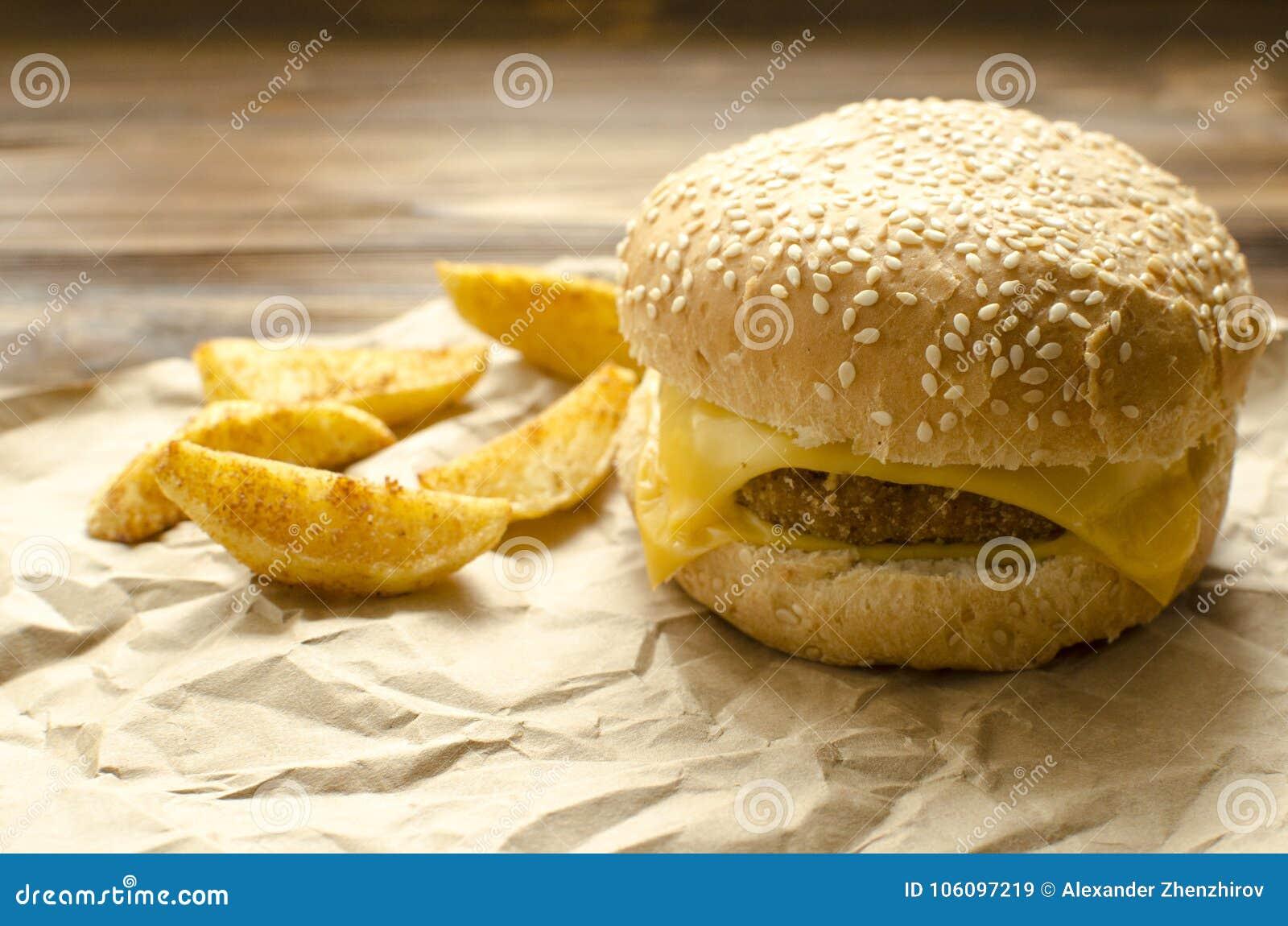 乳酪汉堡用油煎的土豆和辣椒在工艺纸