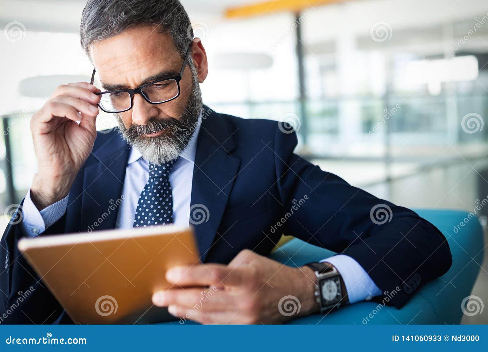 事务、技术和人概念-与运作在办公室的平板电脑的资深商人