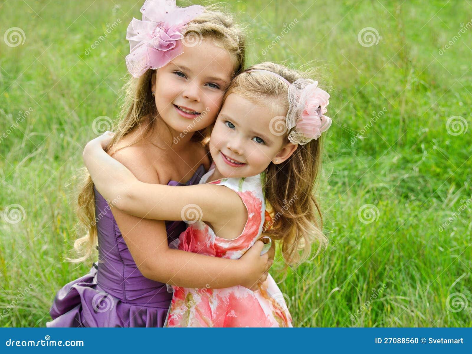 二个拥抱的逗人喜爱的小女孩纵向