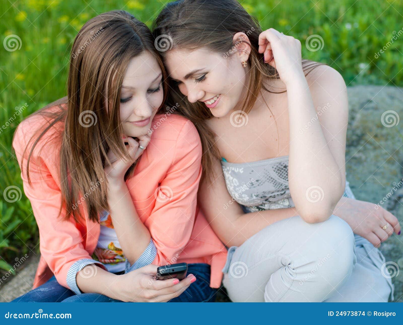 二个美丽的愉快的少妇&移动电话