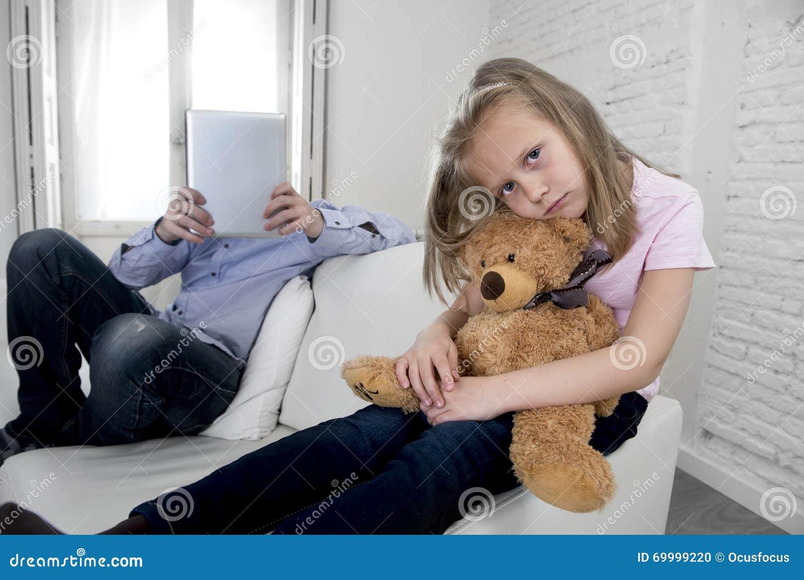 互联网使用数字式片剂垫的上瘾者父亲忽略小哀伤的女儿使拥抱玩具熊不耐烦
