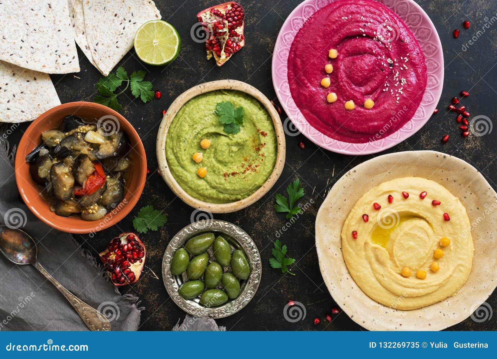 五颜六色的各种各样的hummus、caponata、橄榄、皮塔饼和石榴在黑暗的土气背景 素食饮食食物 顶视图,平