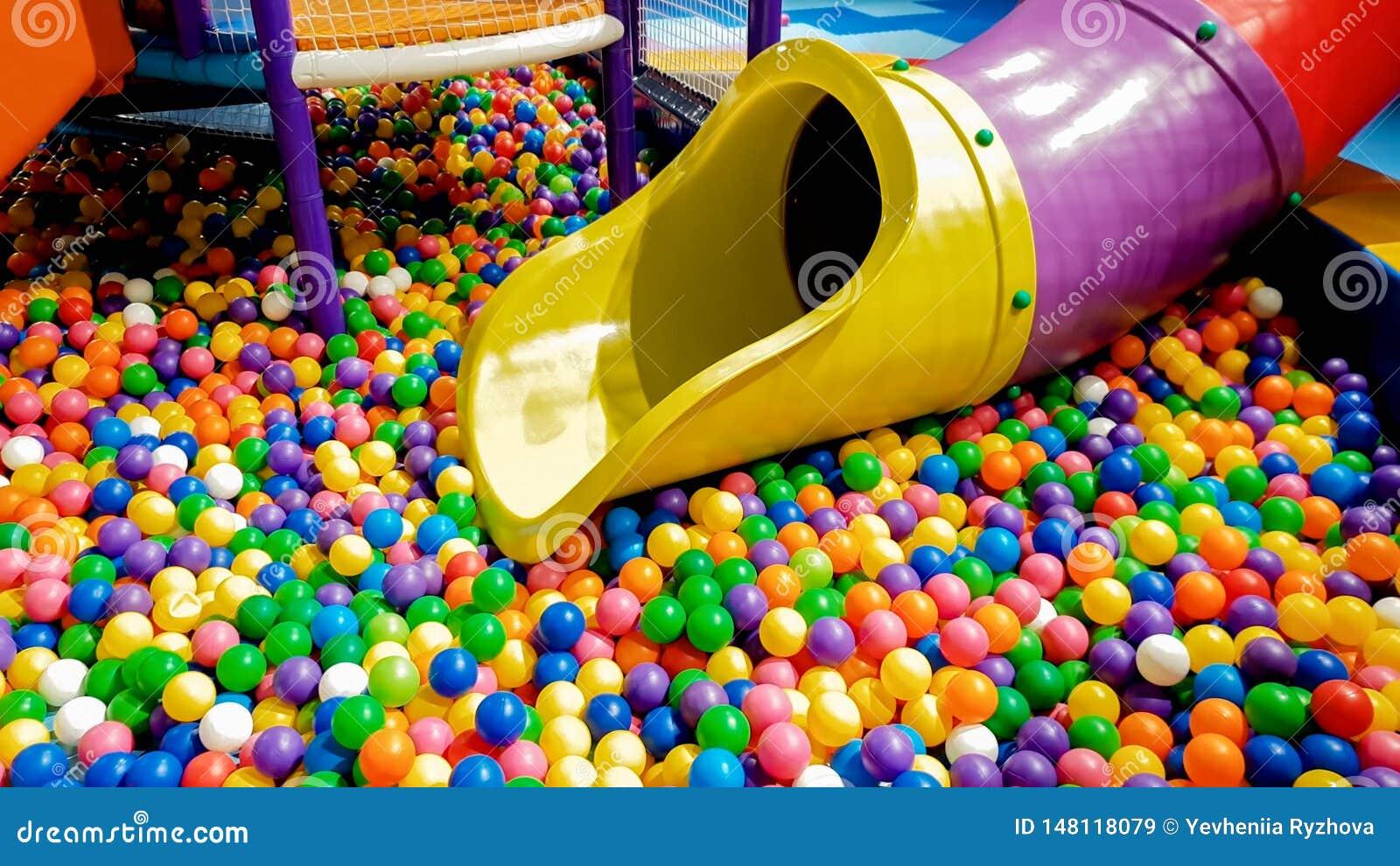 五颜六色的幻灯片的特写镜头图象在儿童操场的有许多的在水池的小塑料球