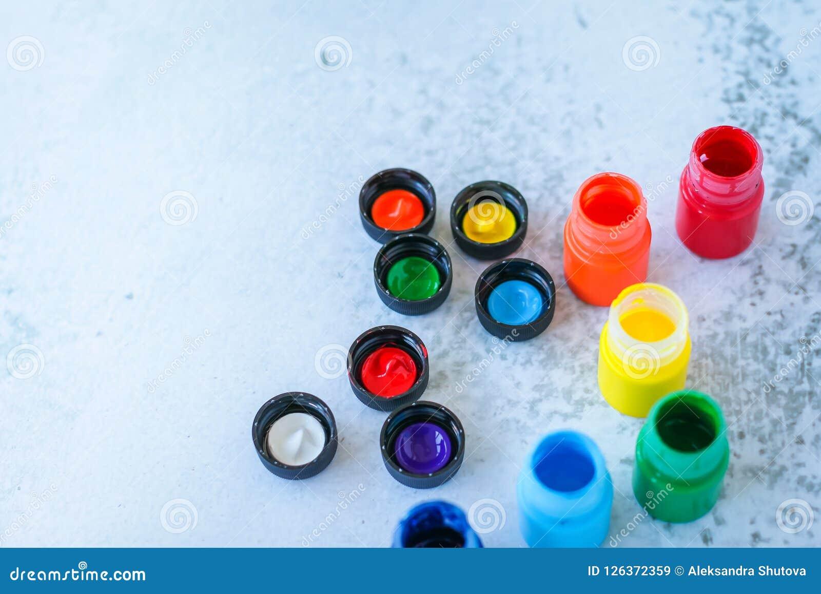 五颜六色的树胶水彩画颜料或丙烯酸漆在瓶子在白色难看的东西背景,选择聚焦