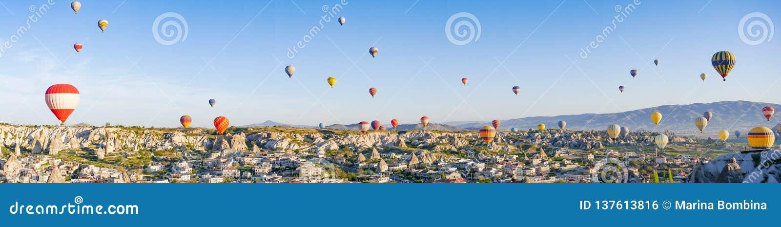 五颜六色的热空气迅速增加飞行在岩石风景在卡帕多细亚土耳其